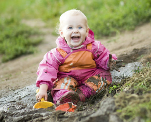 Happy 18-months-old Child playing in Mud
